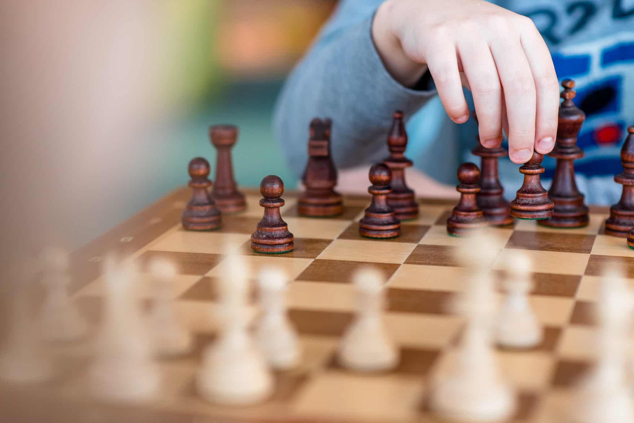 Beginner chess player holding his hand over black chess pieces
